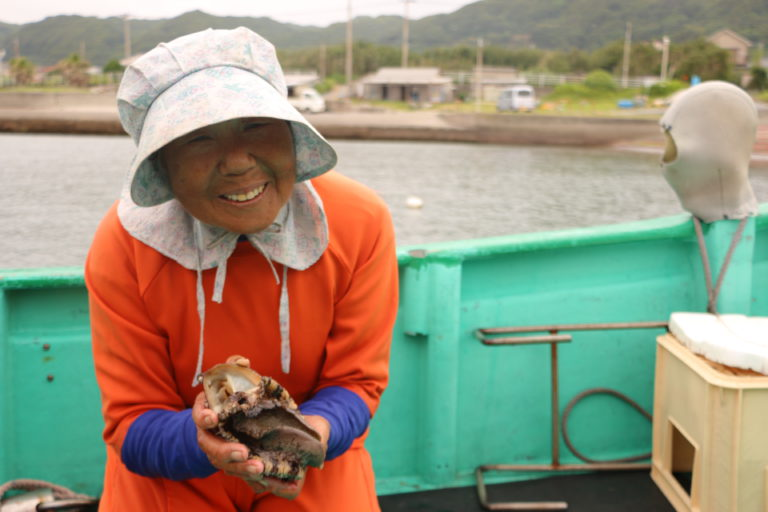 アワビを持つ海女の山岡絹代さん